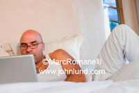 Man using his laptop computer on his bed in his bedroom. The man is bald, has a tattoo on his arm and is dressed in white.